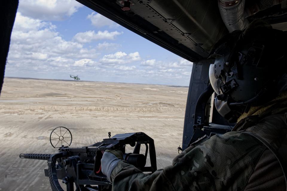 A Royal Marines aviation crewman manning a heavy machine gun