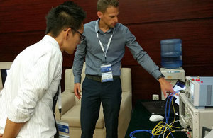Demonstrating the integrated circuit developed by HiLight Semiconductor at a trade show in Shenzhen, China.