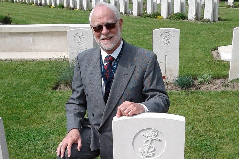 David Slade kneels beside the newly marked headstone for PO McDonald, Crown Copyright, All rights reserved