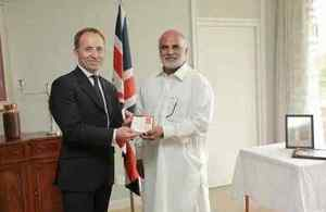 Mr Channu Pervaiz' son, Aslam Pervaiz receiving the British Empire Medal from the British High Commissioner, Thoms Drew