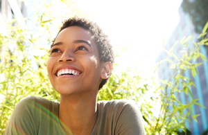 Young woman smiles outdoors. By mimagephotography at Shutterstock