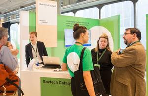 GovTech Catalyst team talking at the Sprint 18 market stall