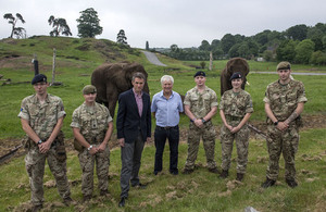 Defence Secretary Gavin Williamson with military personnel standing in front elephants at West Midlands Safari Park