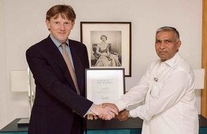 Acting British High Commissioner Richard Crowder presenting the certificate signed by Her Majesty The Queen to Master Ayub.