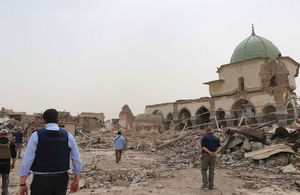Wide shot of five men in blue shirts, some in flak jackets, walking amidst the rubble of buildings.