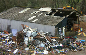 Large derelict building overflowing with rubbish and waste heaped up against its side