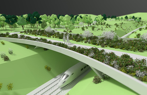 Animation of a train going under a green bridge lined with shrubs with a family walking across it.