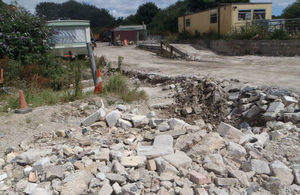A quarry-like site with industrial shed and broken rocks littering the road