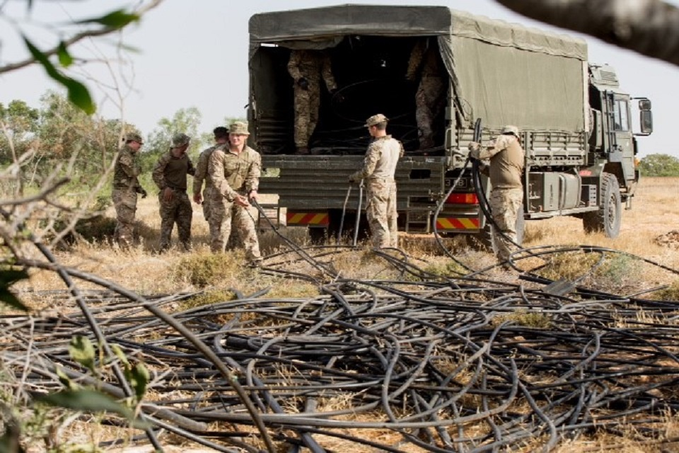 British forces load irrigation pipes into a vehicle.