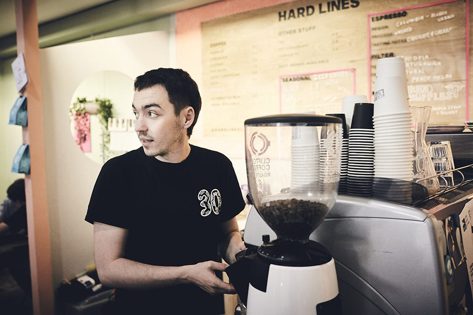 Man at coffee machine, grinding beans. Stands in front of Hard Lines wall menu.