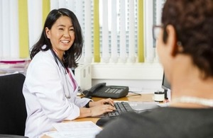 Smiling doctor looks at patient as she types on a keyboard
