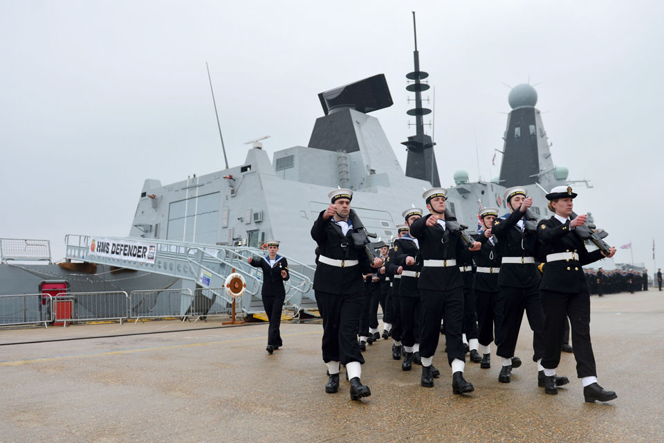 A ceremonial guard marches past HMS Defender
