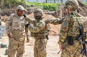 British Royal Engineers in military uniform discuss the construction of a bridge with an Iraqi security force (ISF) member in Mosul, Iraq.