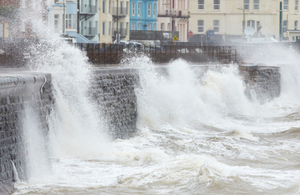 Waves crashing against a sea wall (Credit: Getty Images)