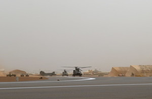 Three Chinook helicopters on a runway in Mali. The background is hazy and there are tents in the background that are desert-camouflaged