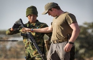 A female member of the Nigerian Air Force stands guard over a British soldier during a role play exercise run by the British Military Advisory Training Teams Short Term Training Team.