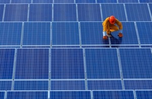 A technician works on solar panels via W Joke khumkhur at Shutterstock
