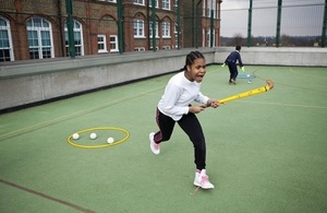 Girl playing hockey in a school playground
