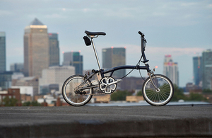 Brompton bike with city skyline in background