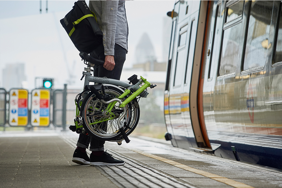 Man holding folded Brompton bike before getting on underground train