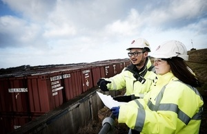 Two members of the LLWR workforce in hard hats, safety gloves and jackets look out over Vault 9 on the Repository Site