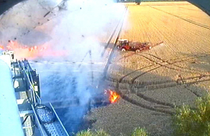 image of fire near the roadside and fields