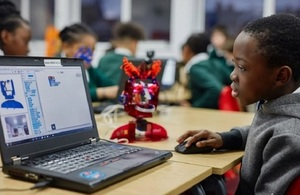 Image of school child learning to code using the Ohbot robot technology.