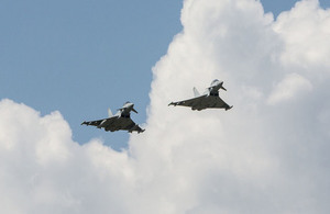 Two typhoons are flying against a blue sky.