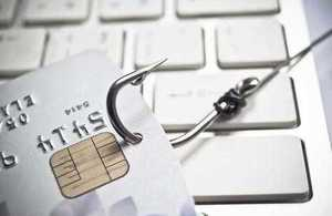 Credit card with fishing hook to illustrate phishing scam