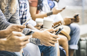 A row of people holding coffee cups and using their smartphones.