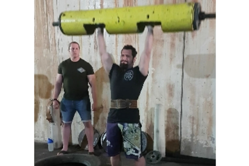Temporary Police Sergeant Mark Bunce doing a log press.