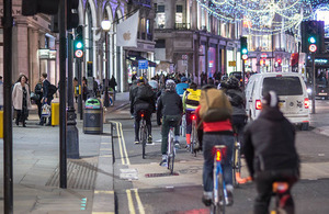 Picture of cyclists on roads, cars and pedestrians.