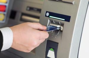 A man putting a bank card into an ATM machine.