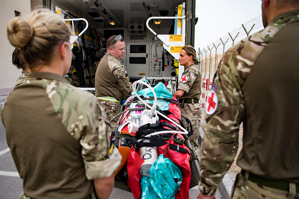 Members of the Joint Medical Group prepare to load a simulated casualty into an ambulance