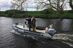 Image shows fisheries enforcement officers on a boat patrol