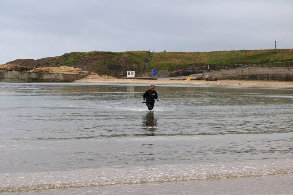 The image shows the Environment Agency's Mick Donkin collecting samples at Cullercoats