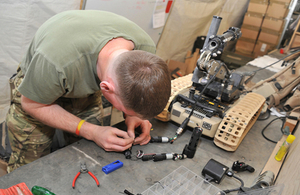 The image shows a male soldier fixing a wire that is linked to a small vehicle the size of a waste paper bin.