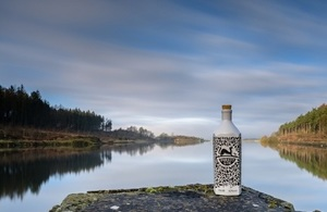 Picture of Forest Gin bottle in front of lake.