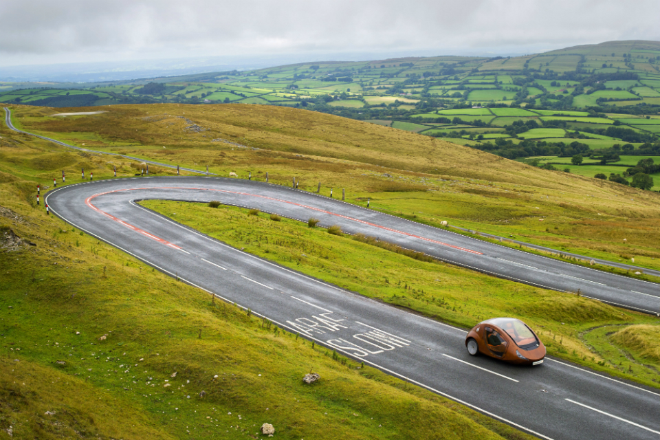 Electric vehicle driving through Welsh countryside