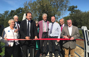 Picture of Jesse Norman cutting a red tape with delegates at Aylesbury Station and Waddesdon Manor.