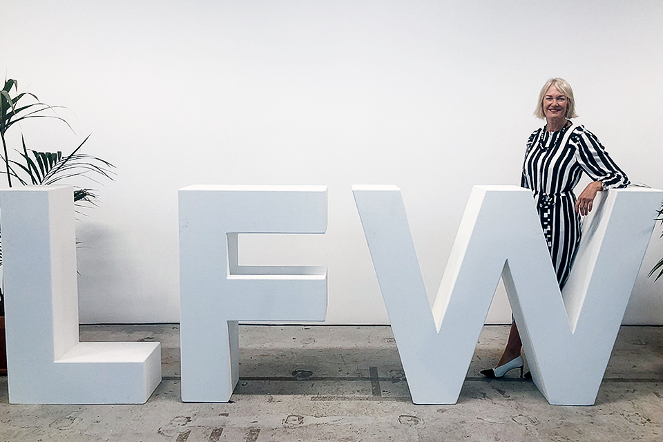 Image of the Minister for Digital and the Creative Industries in front of the London Fashion Week sign.