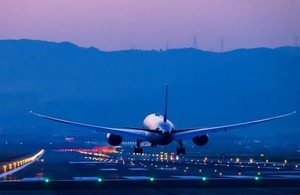Boeing airplane lands at dusk via motive56 at Shutterstock