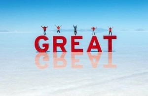 People jumping on GREAT letters on Bolivian salt flats