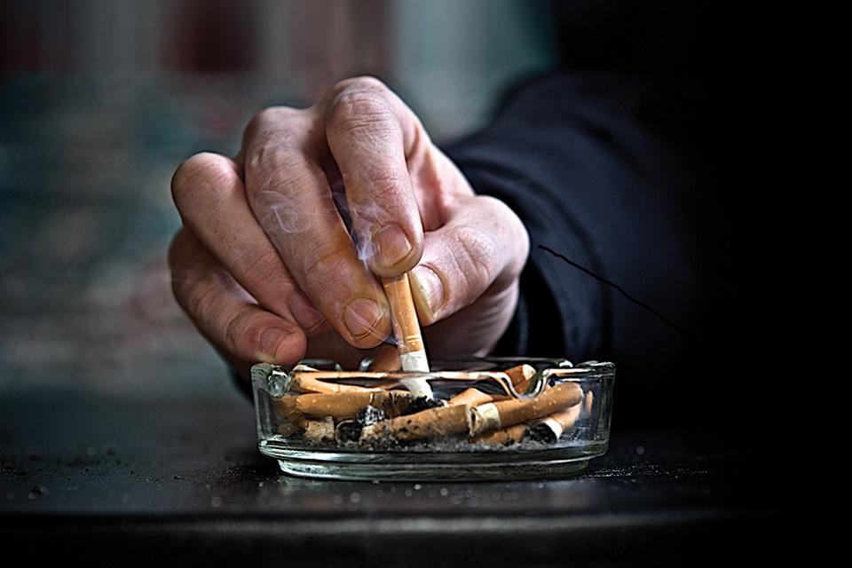 Hand stubbing out cigarette