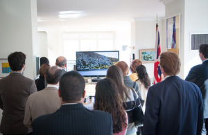 The crowd looks on at the promotional video.