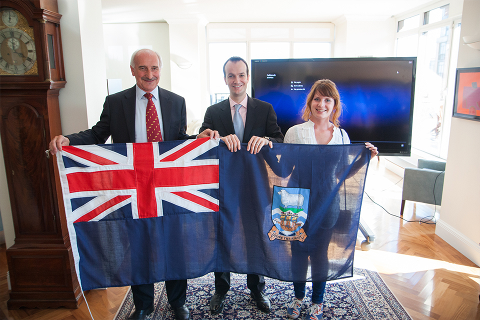 Mike Summers, Danny Lopez, and Teslyn Barkman hold the Falkland Islands flag.