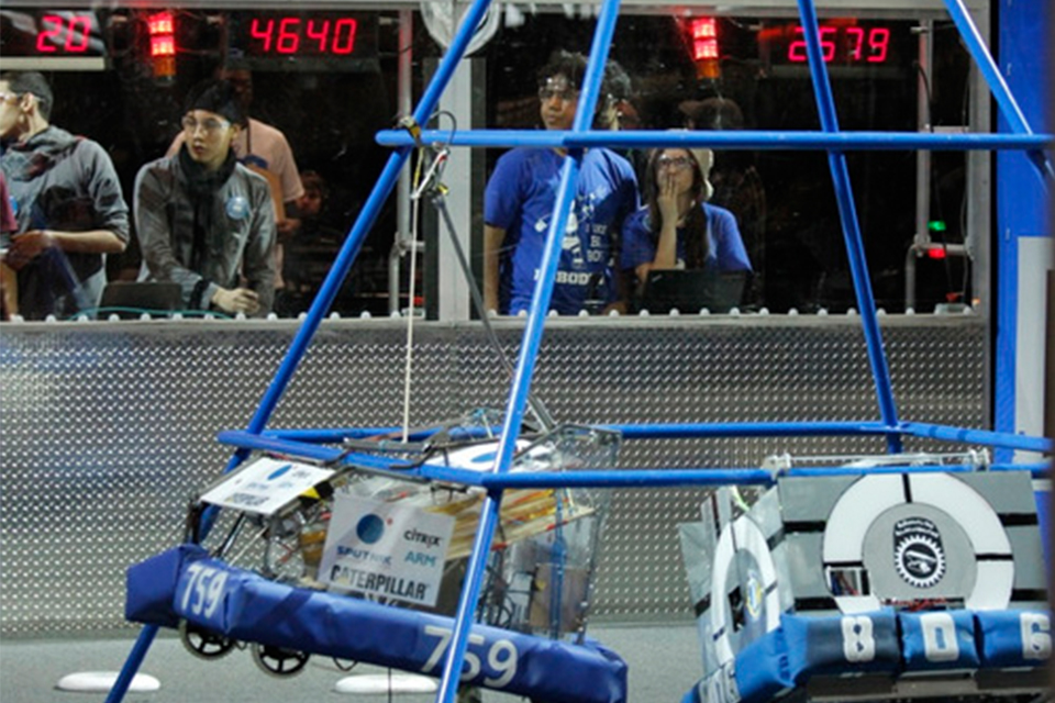 The team's robot climbs a tower.
