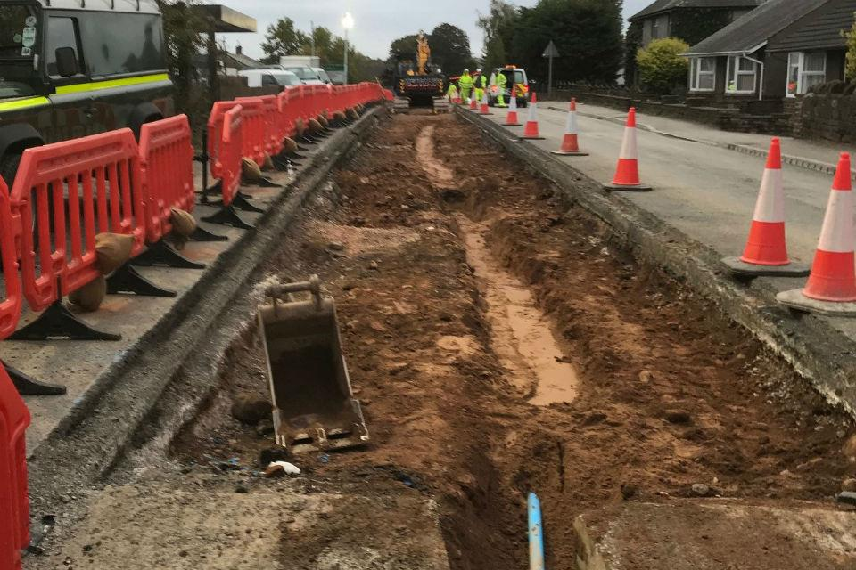 Road workers laying a new water pipe near houses west of Main Street at Kirkby Thore.