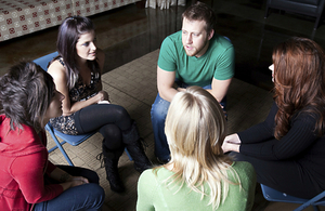 Five people facing each other in discussion