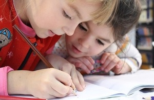 Two primary school pupils writing in a book.
